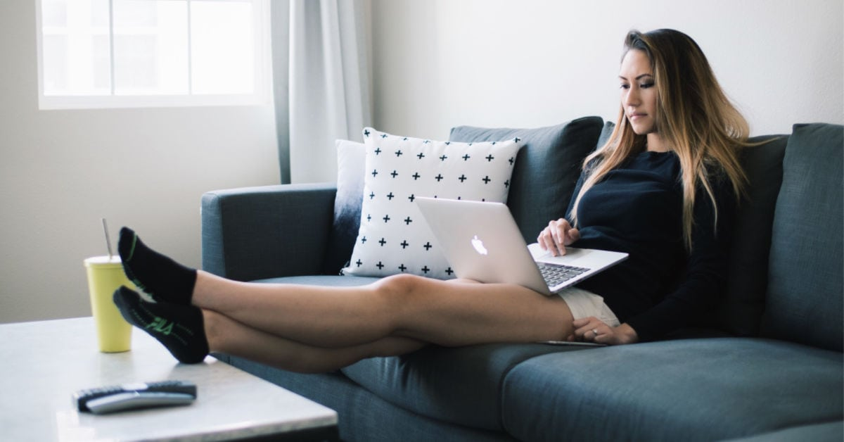 college girl studying on the couch with her feet up