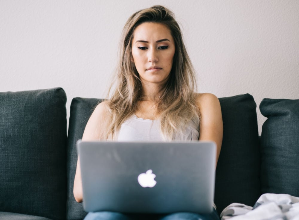 female college student concentrating while studying on her laptop