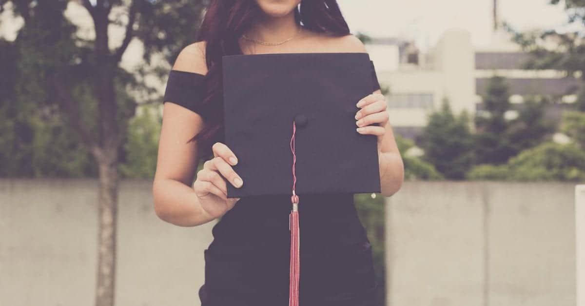 teen girl holding grad cap in front of her