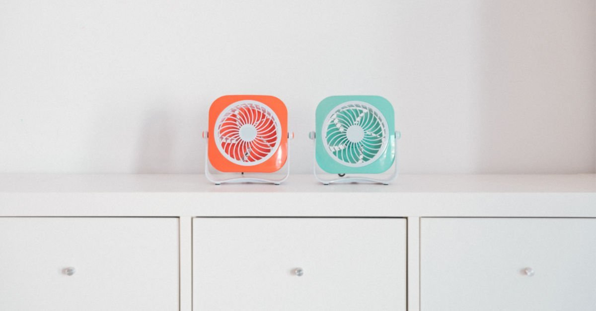 orange and teal fan on white dresser