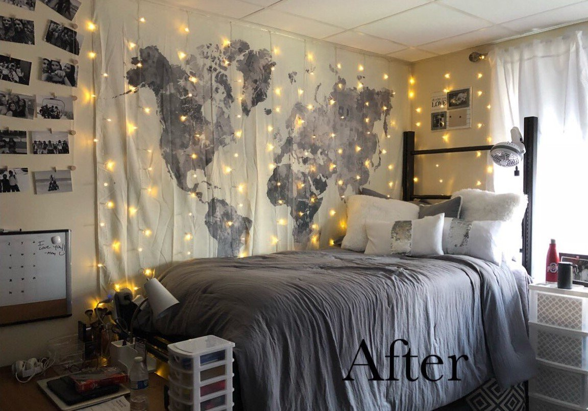 dorm room after makeover - decorated with world map tapestry, grey decor, and string lights