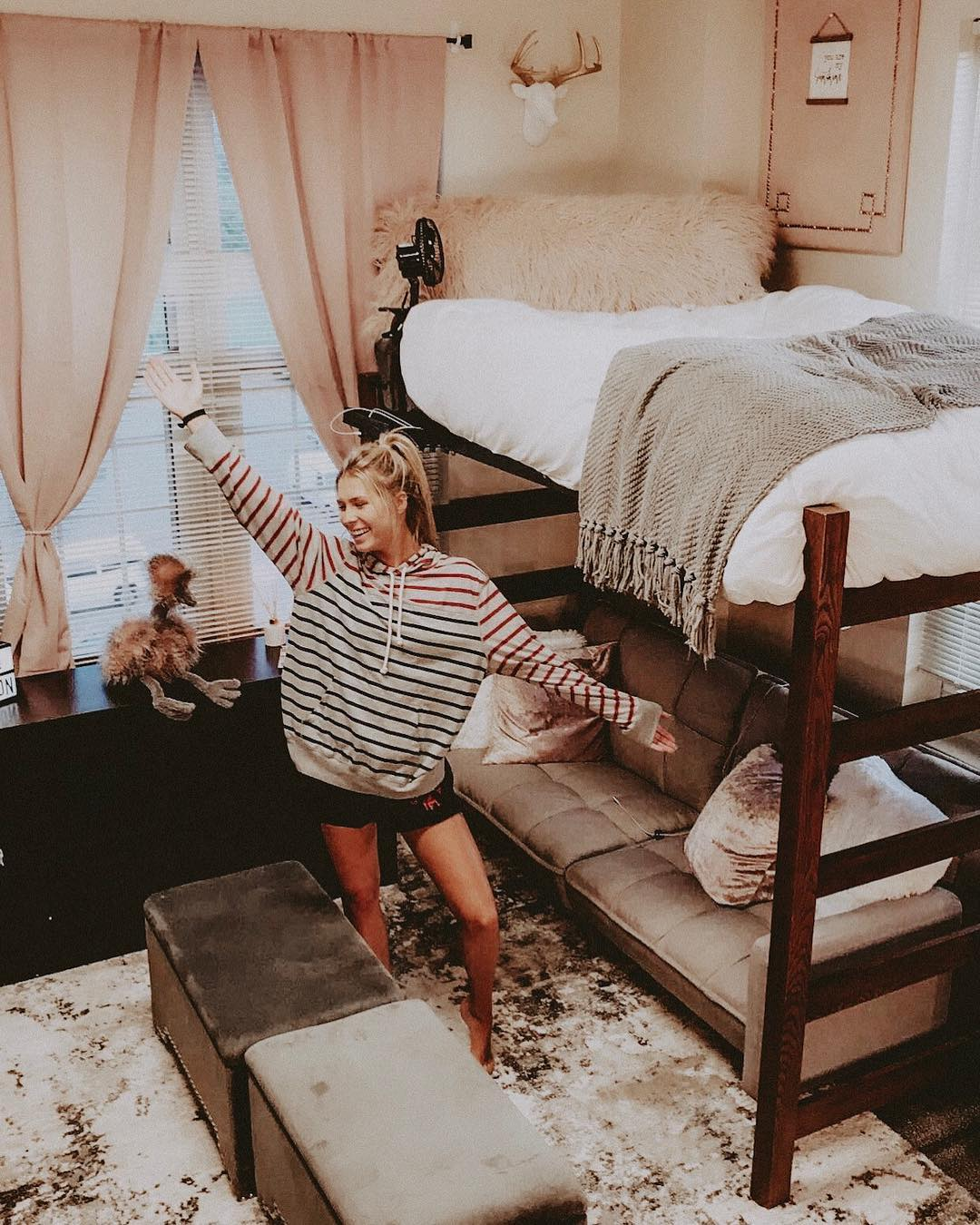 college girl posing in her dorm room with her arm up. Room decorated with grey, soft looking things