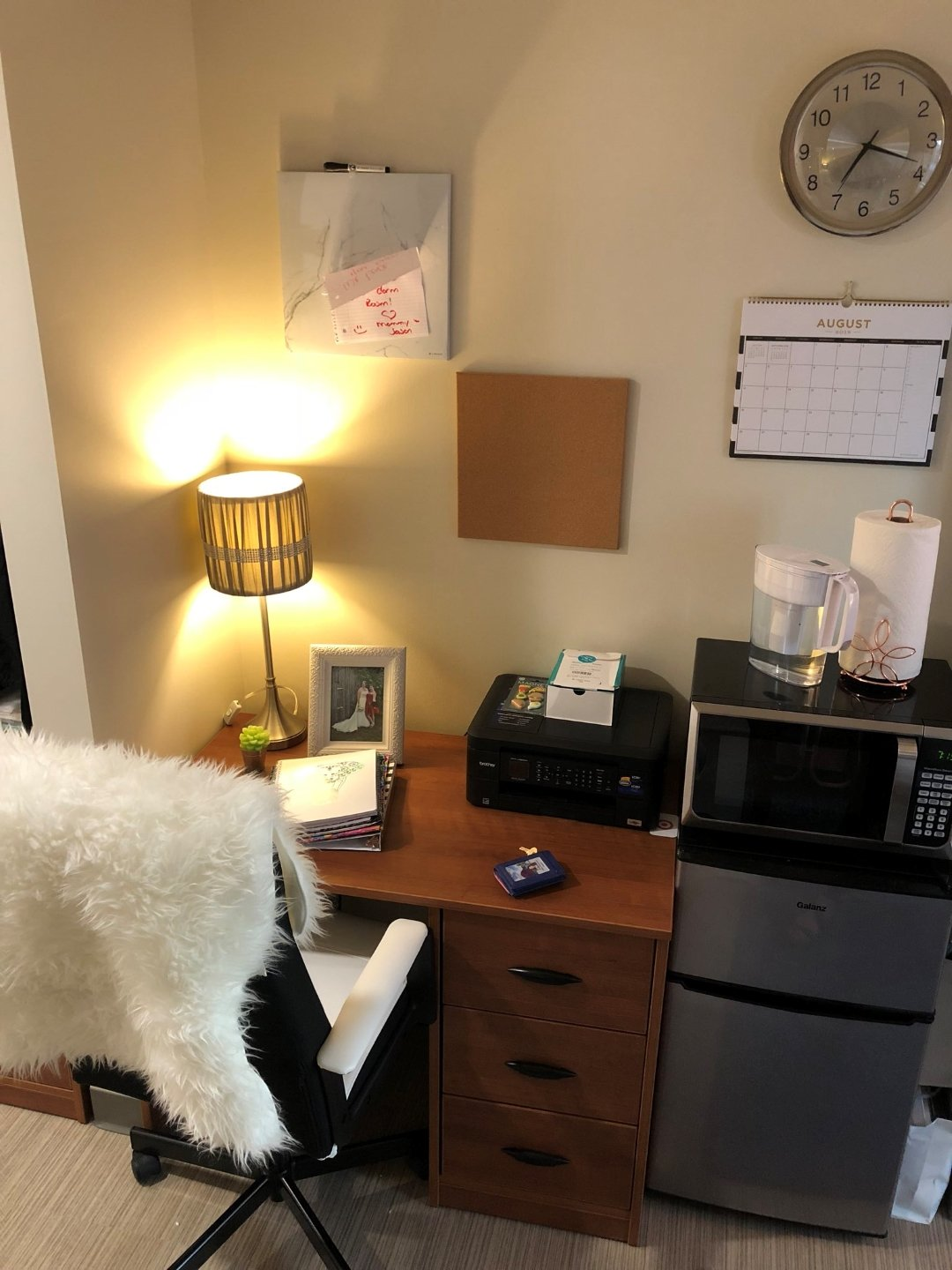 college dorm desk, mini fridge, and microwave. chair with faux fur covering