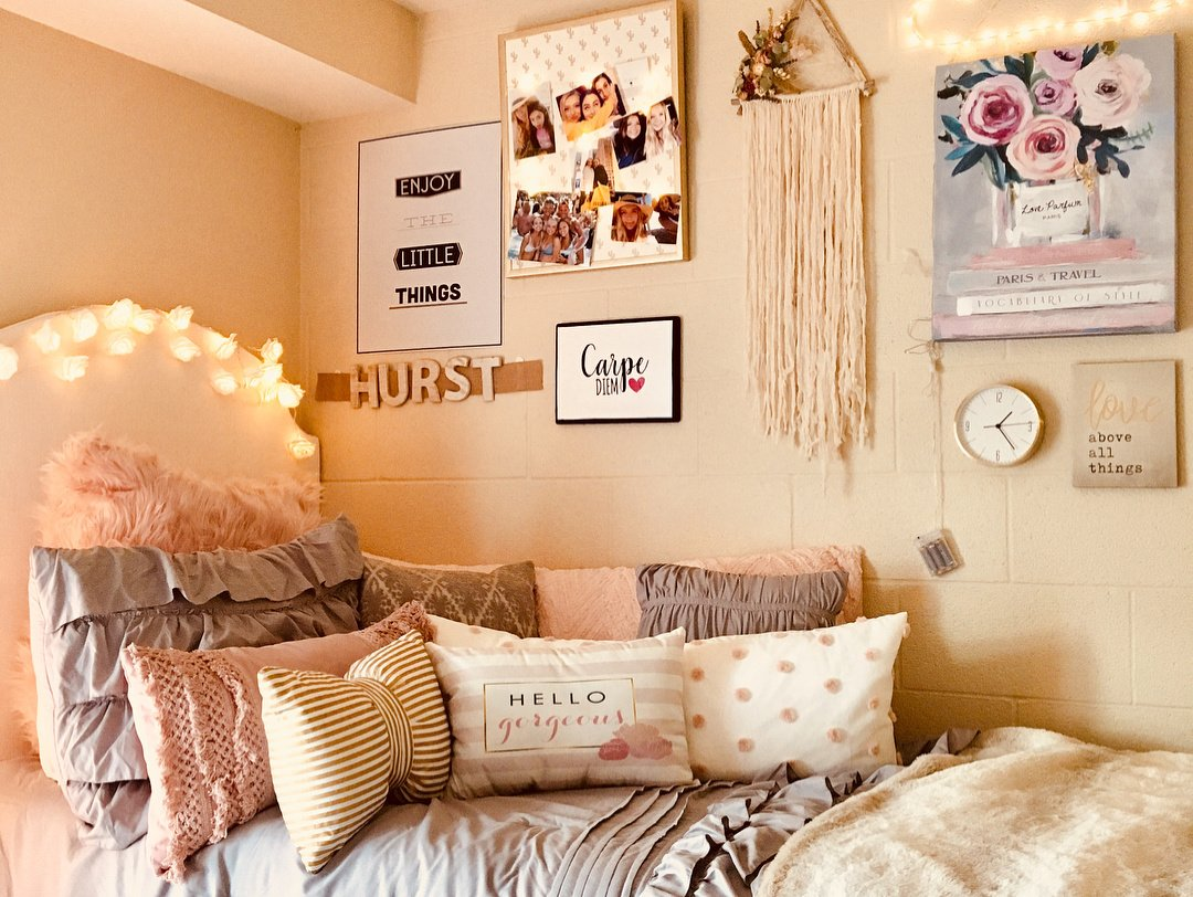 dorm room bed with pink and gray bedspread + wall decor (art, macrame)