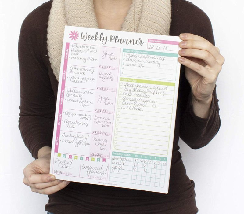 woman holding bloom weekly planner for students