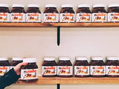 young woman's hand reaching up to grab a nutella jar next to more on shelves