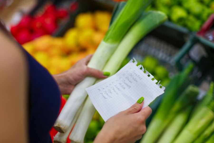 woman holding handwritten grocery list in in one hand and vegetable in other hand at the supermarket