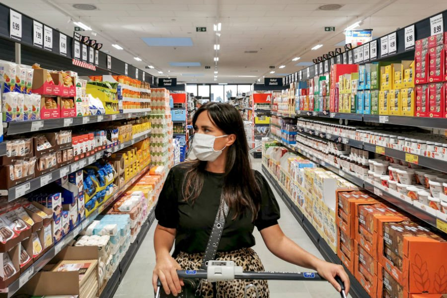 college girl wearing mask while looking for food to buy in an isle at the grocery store