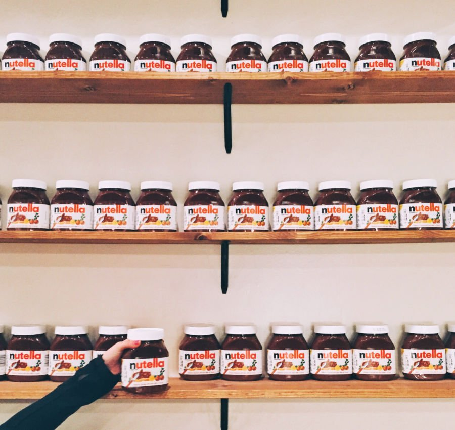 jars of nutella on shelves with a hand reaching up to grab one