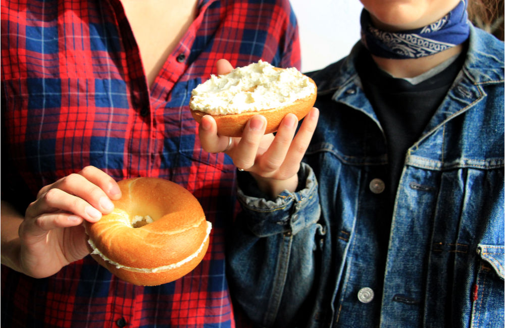 people holding bagels with cream cheese