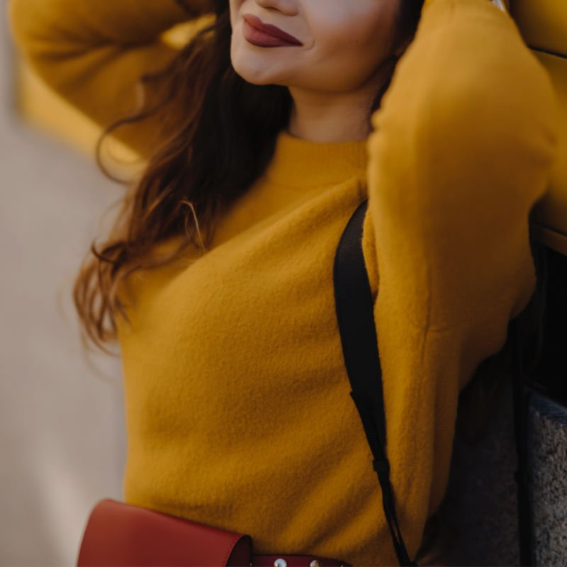 woman in yellow sweater smiling red lipstick