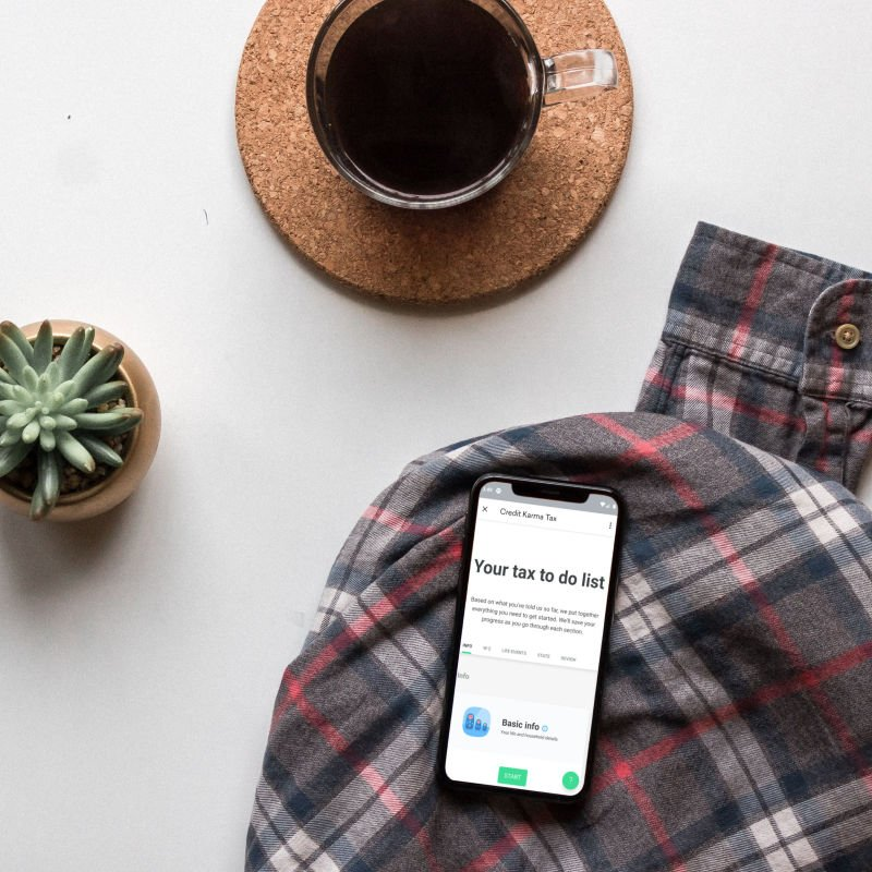 Credit Karma Tax on smartphone, flatlay with coffee and plant