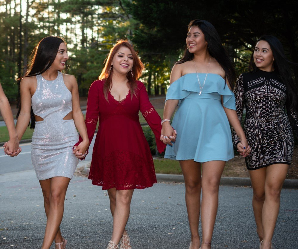 group of women in dresses holding hands for formal