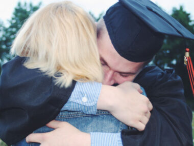 guy wearing graduation cap and gown hugging his mom