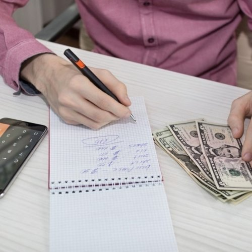 guy writing down his budget