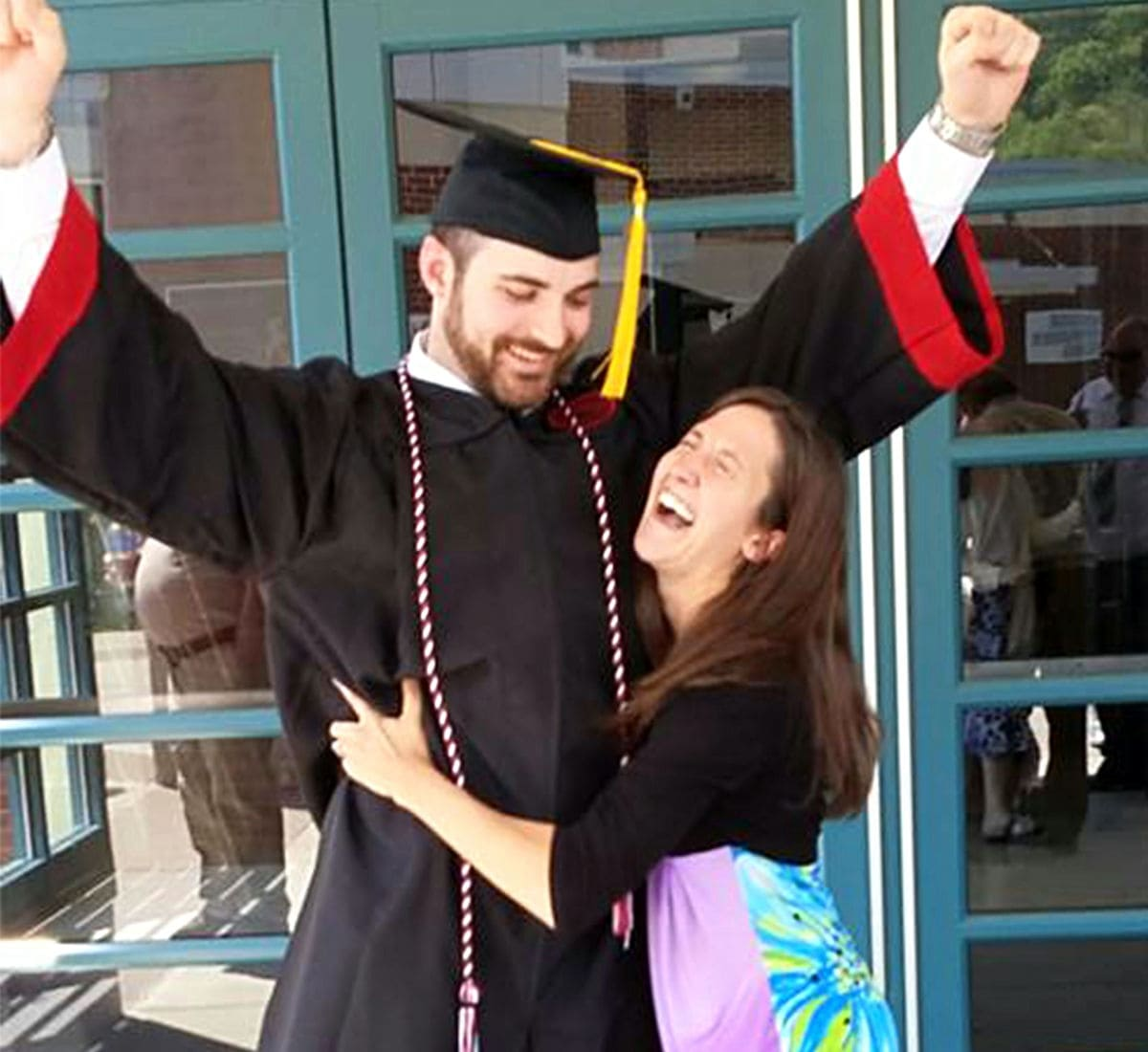 college guy in graduation cap and gown with his arms up while his mom is hugging him and laughing