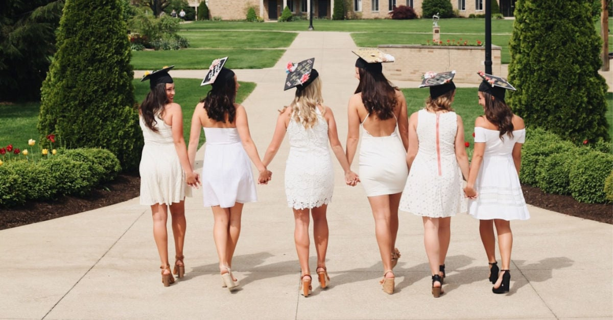 group of high school girls holding hands and wearing graduation caps