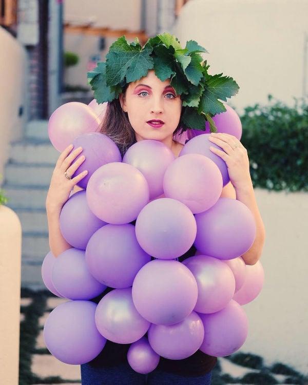 girl wearing purple balloons for grape costume