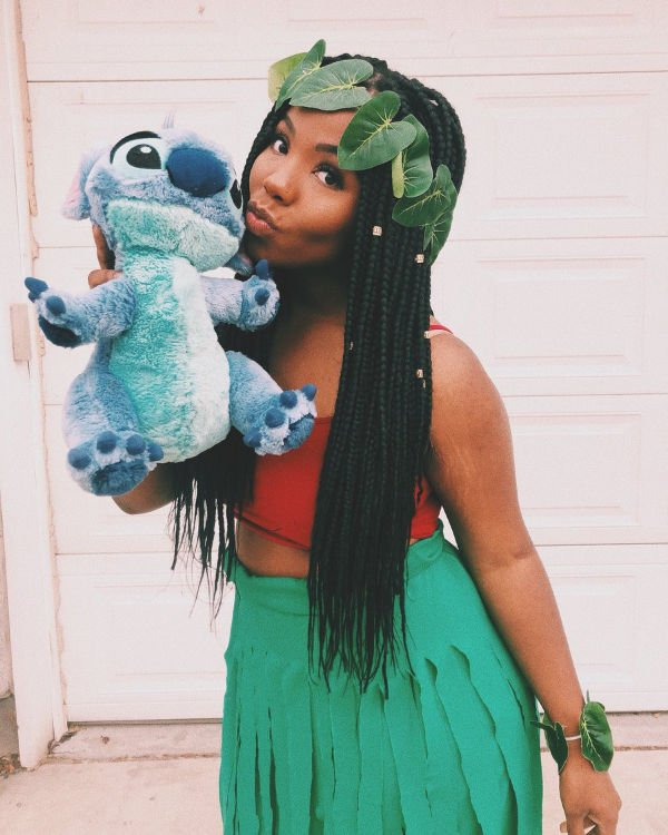 Girl in Lilo grass skirt costume holding Stitch