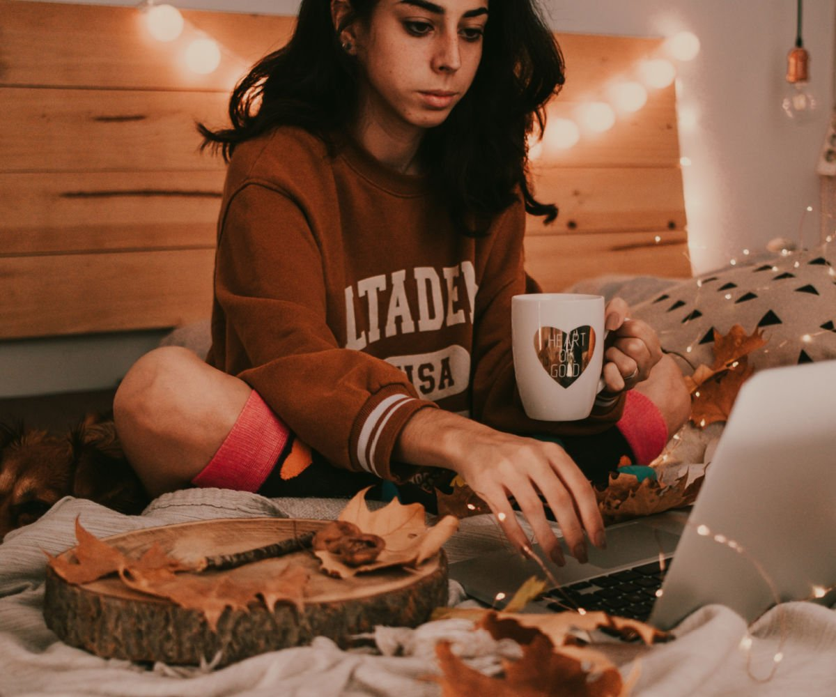 female college student with laptop on bed wit October decor
