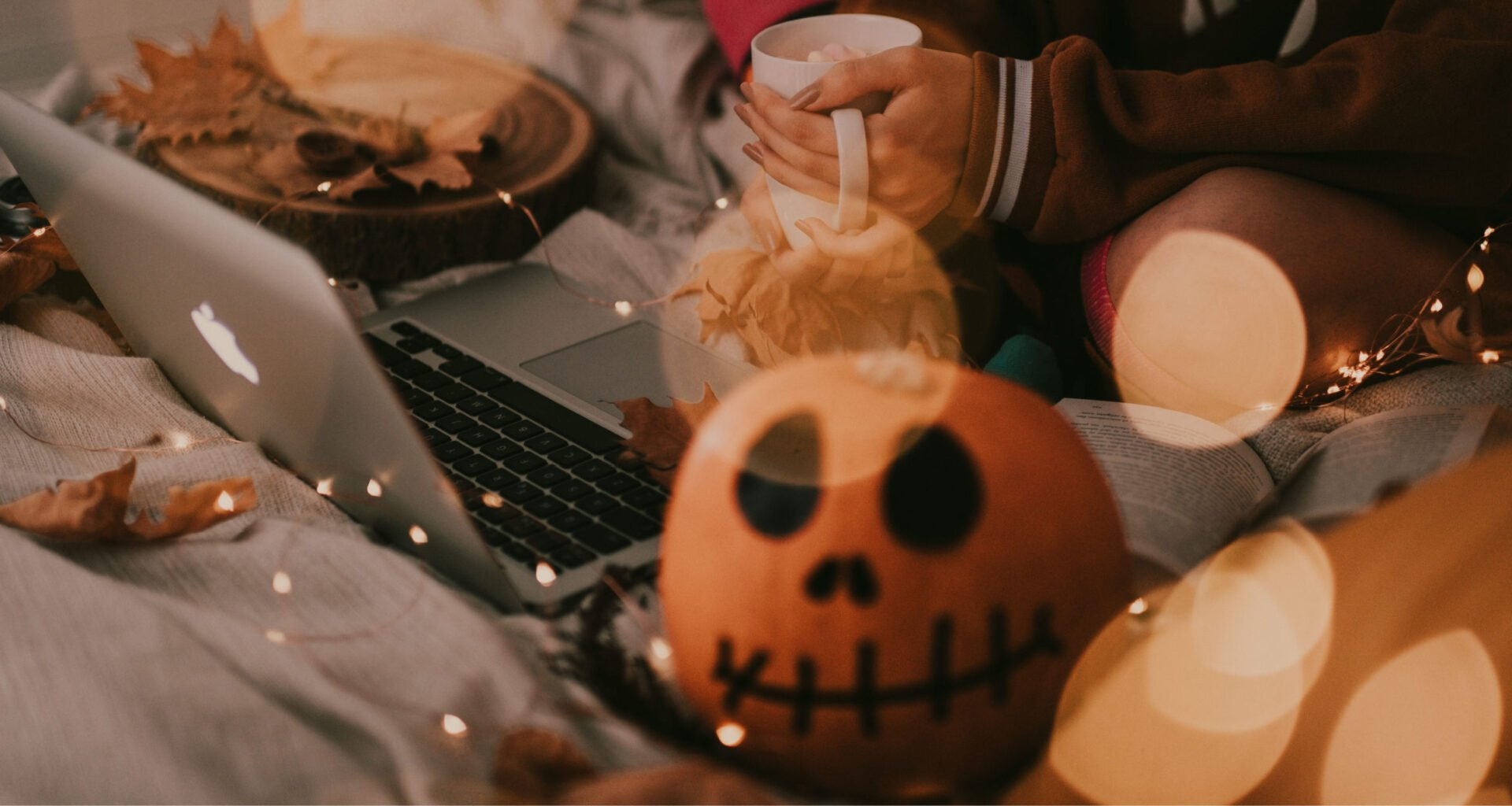 student using laptop on bed surrounded by Halloween decor and pumpkin with face drawn on