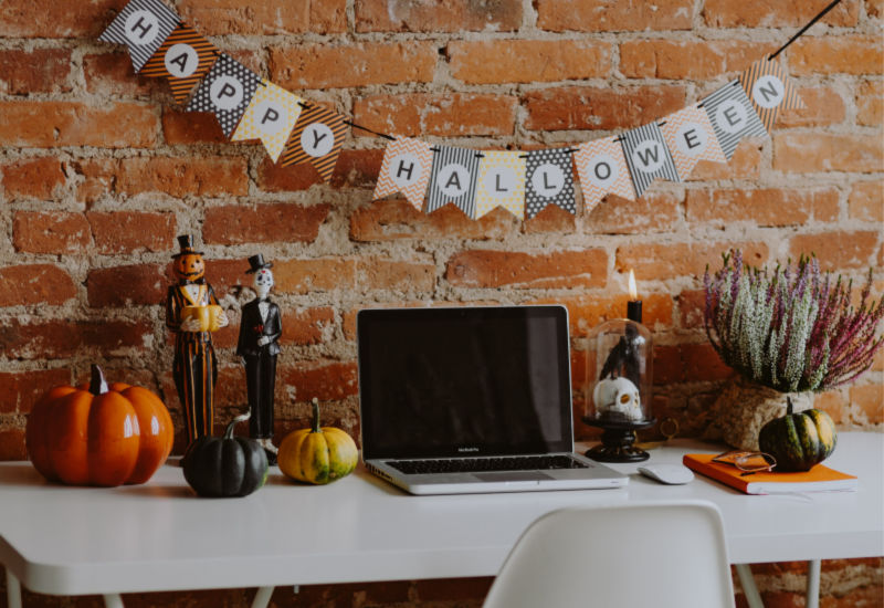 "laptop on desk with ""Happy Halloween"" banner on wall"
