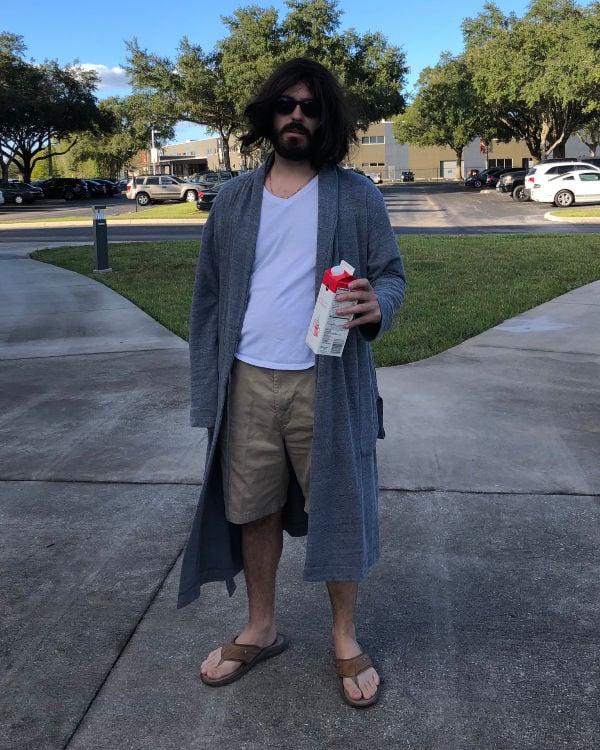 cguy in blue bathrobe, flip flops, holding a carton of milk