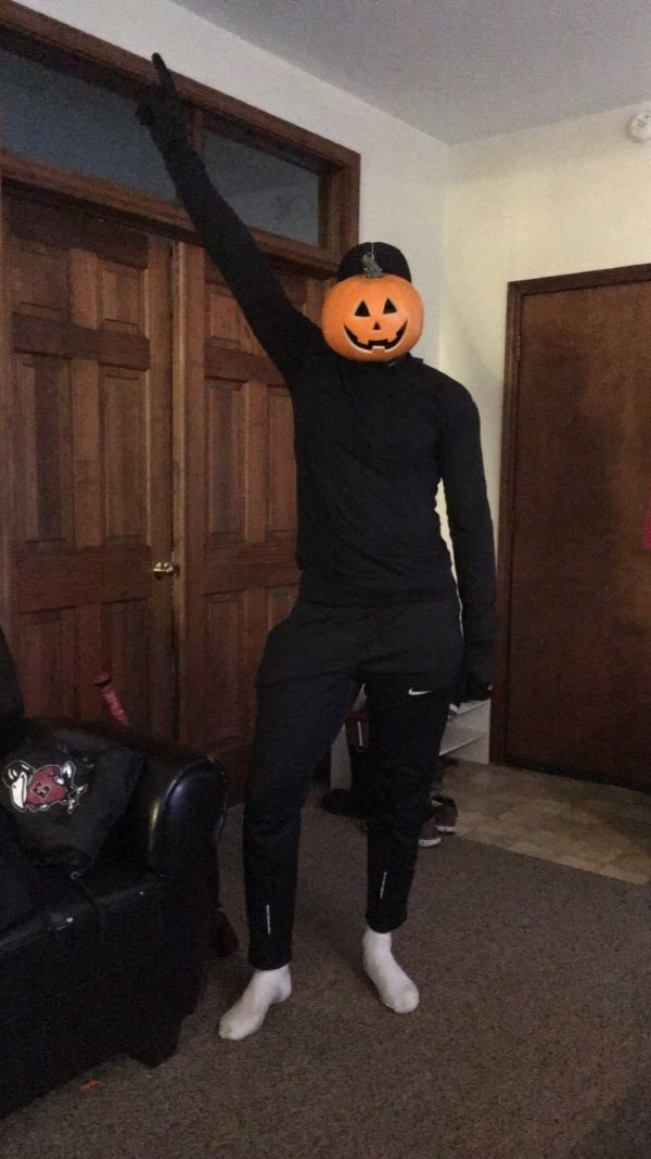 guy in all black with pumpkin face mask