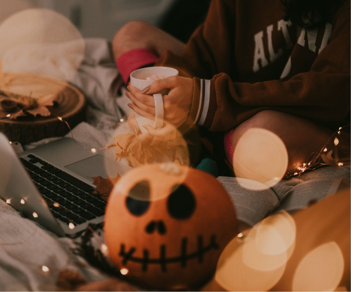 Halloween decorated pumpkin with girl working on laptop in background
