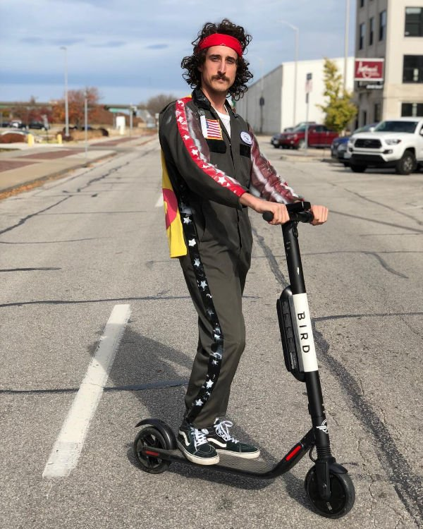 man in jumpsuit with a cape on a scooter