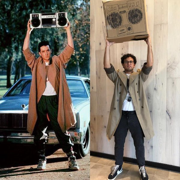 guy in a trench coat holding a cardboard boom box