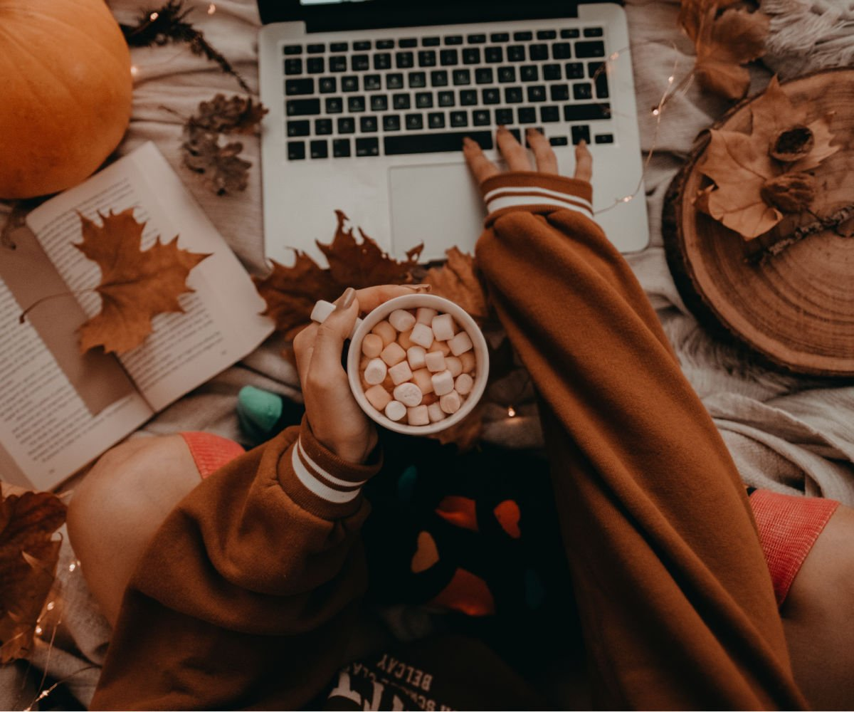 college girl holding cup of hot cocoa in orange sweatshirt applying for scholarships on laptop