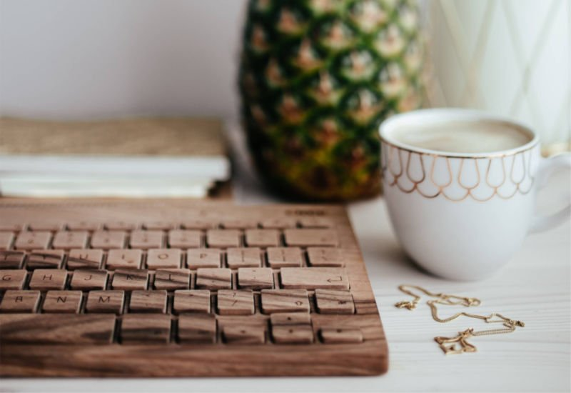 keyboard on a white desk, pineapple, white coffee cup