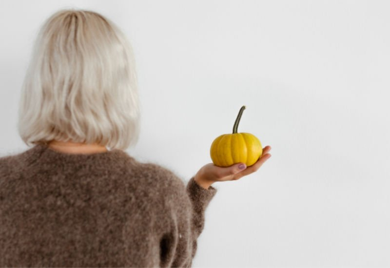 white haired woman with small yellow pumpkin in hand