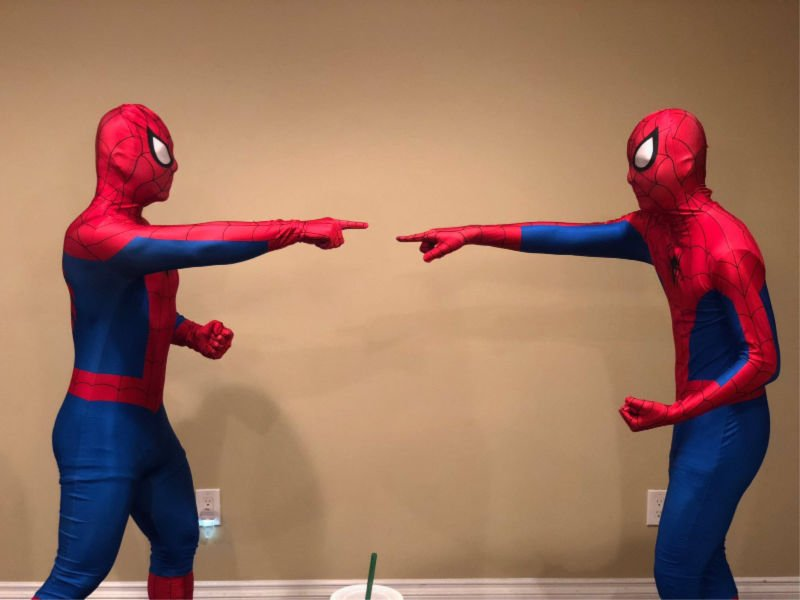 two guys dressed as spiderman pointing at each other