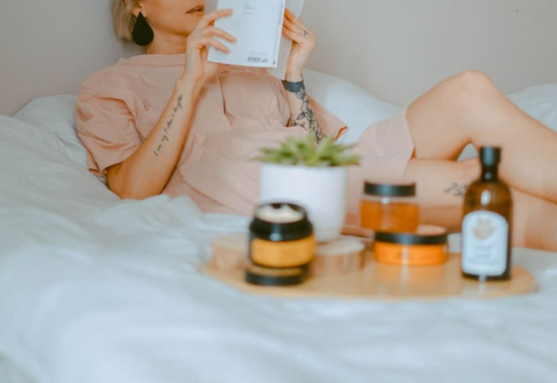 woman relaxing on a bed with self care items