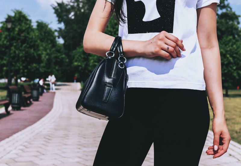 woman holding a black purse on her forearm