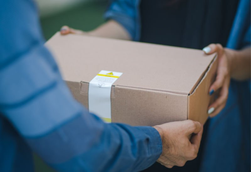 a brown package being handed to a woman from a man