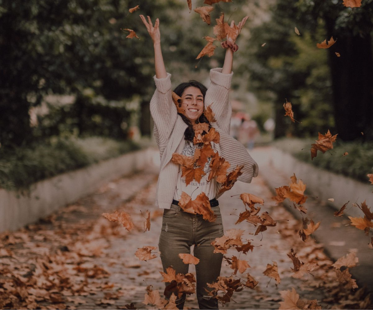 college girl happily tossing brown fall leaves in the air