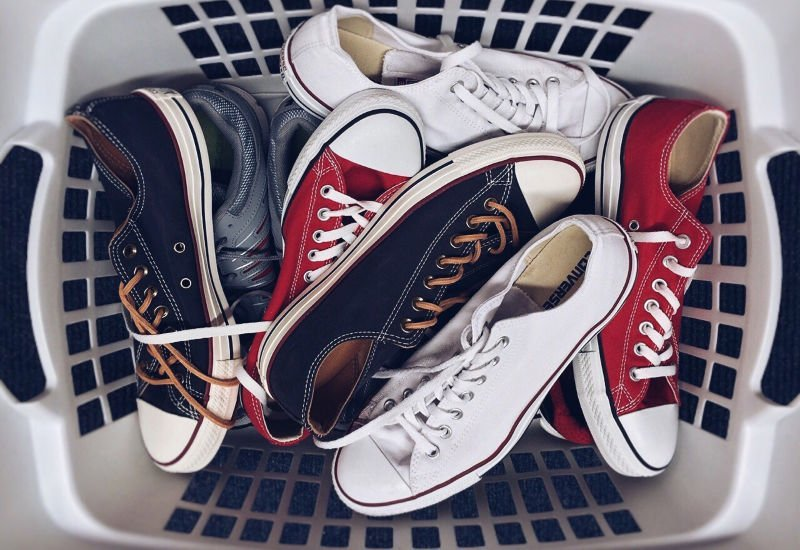 laundry basket full of converse shoes