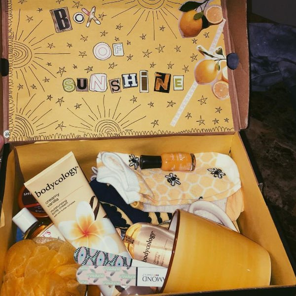 an example of a box of sunshine. it has lotion, nail polish, socks, a yellow mug and some other things