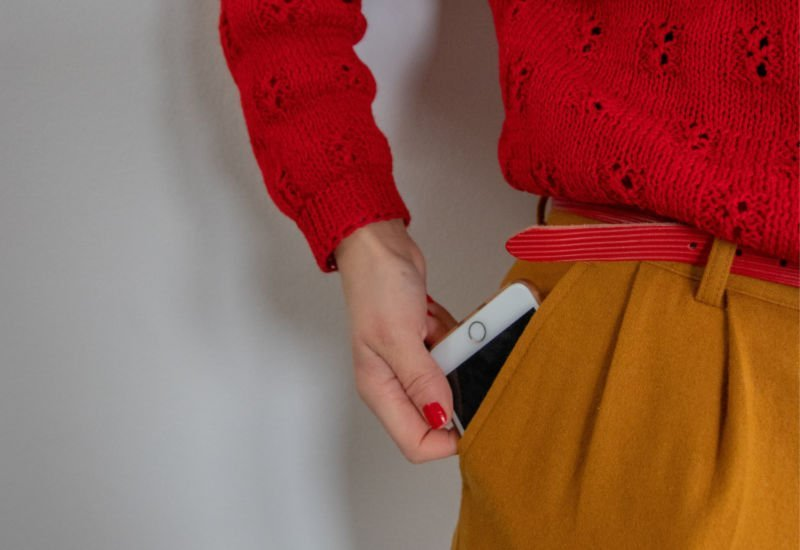 woman pulling a phone out of her pocket to search for college scholarships