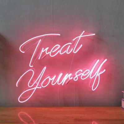 """real glass neon sign that reads """"treat yourself"""" in pink"""