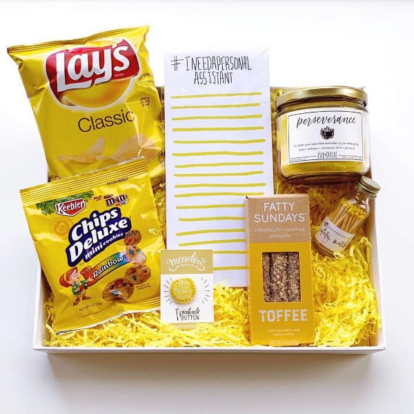 lay's chips' toffee pretzels, a candle and other yellow things in a box with
