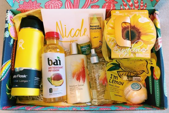 birthday gift box with yellow things like a candle, lotion, and a bath bomb