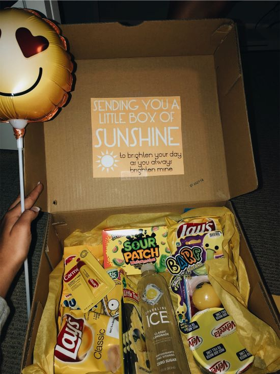 """care package with yellow items, note that reads """"sending you a little box of sunshine"""""""