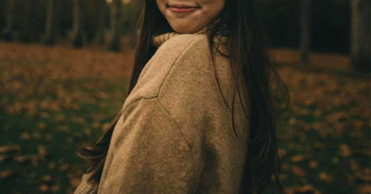 girl in an oversized yellow jumper smiling