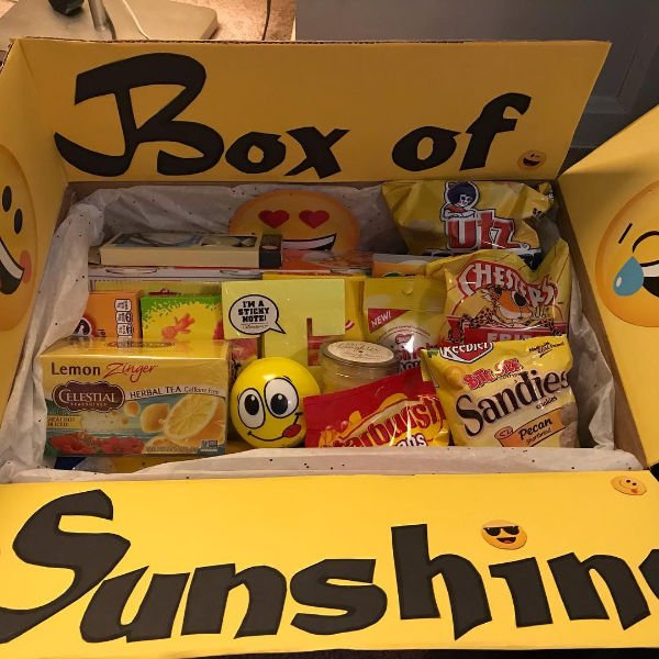 "yellow lined care package that reads ""Box of Sunshine"". Tea, Starburst candy, an emoji stress ball and other items are what's in it"