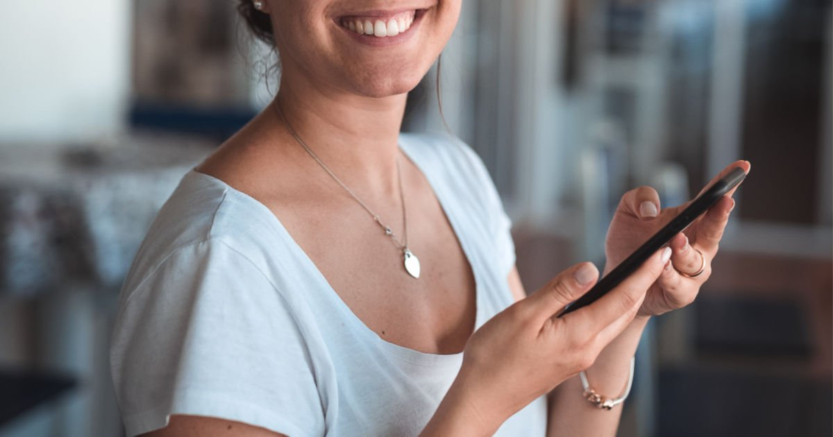 woman smiling and looking a phone