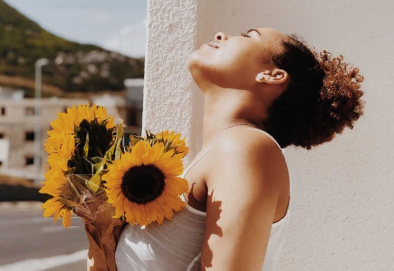 woman smiling with her head back while holding a gift of yellow sunflowers